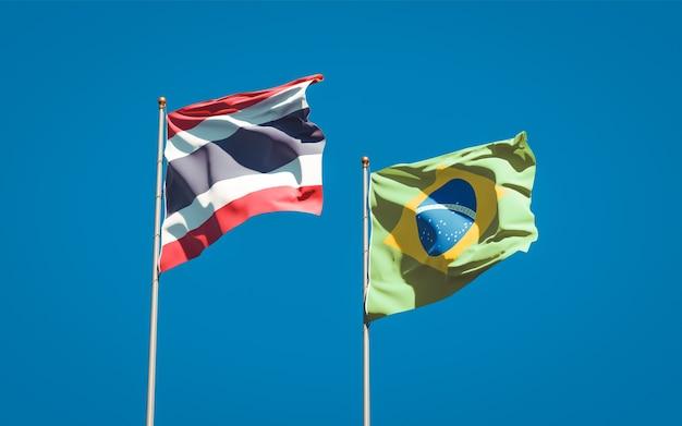 Belle bandiere di stato nazionali della thailandia e del brasile insieme sul cielo blu Foto Premium