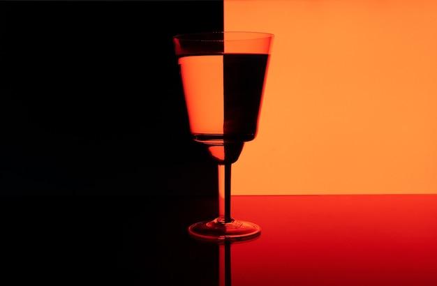 Bella foto di un bicchiere con un drink su uno sfondo nero e rosso con riflessi Foto Premium