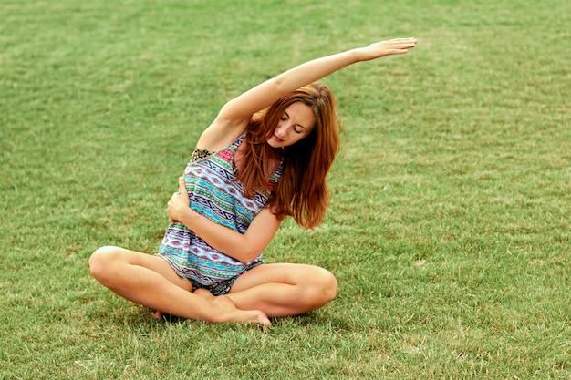 Bella donna graziosa che fa esercizi di yoga nel parco. concetto sano e yoga. fitness e sport Foto Premium