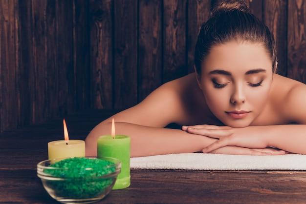 Bella donna abbastanza giovane che risiede nel salone della stazione termale con gli occhi chiusi e rilassati Foto Premium