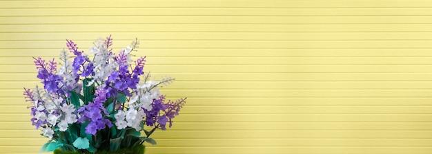Il bello mazzo porpora del fiore di plastica artificiale del lillà o della lavanda in vaso grazioso sulla banda ha strutturato la decorazione gialla del fondo della carta da parati nella stazione termale domestica Foto Premium