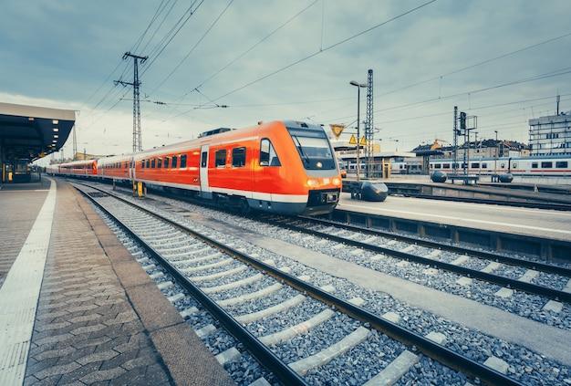 Bella stazione ferroviaria con moderno treno pendolare rosso ad alta velocità. ferrovia con tonalità vintage. treno alla piattaforma ferroviaria. concetto industriale Foto Premium