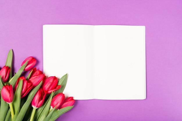 Bei tulipani rossi e taccuino aperto con carta in bianco su fondo porpora. buona festa della mamma. spazio per il testo. biglietto d'auguri. concetto di vacanze. copia spazio, vista dall'alto. compleanno. copia spazio. vista dall'alto Foto Premium