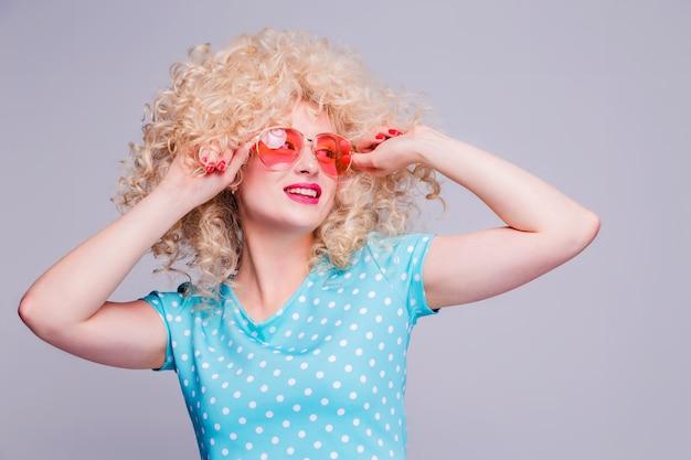 Bella ragazza bionda in stile retrò con voluminosa acconciatura riccia Foto Premium