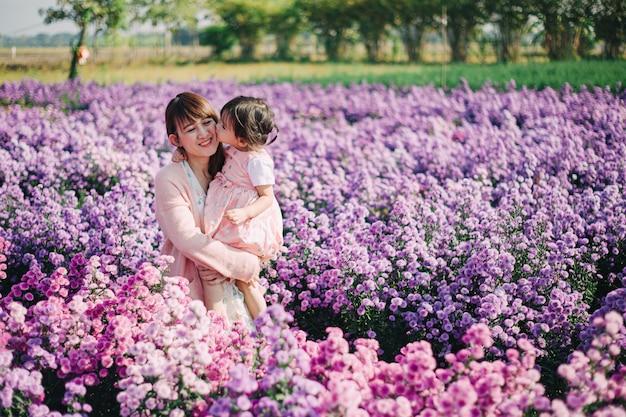 Bella e romantica foto della madre e dei suoi bambini che giocano insieme nel giardino di fiori. Foto Premium