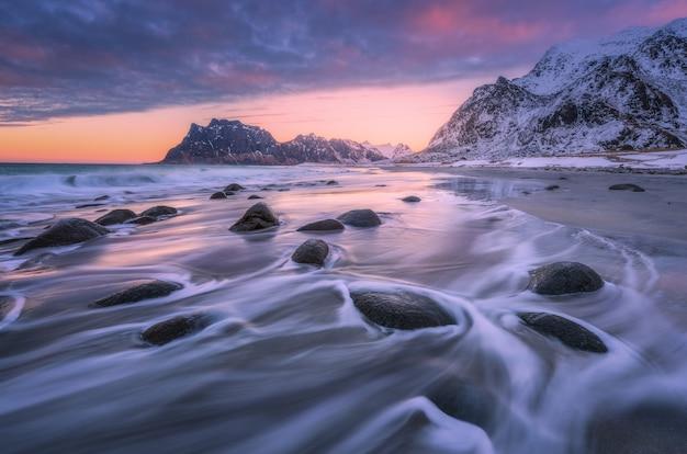 Bella spiaggia sabbiosa con pietre in acqua offuscata, colorato cielo nuvoloso rosa e montagne innevate al tramonto Foto Premium