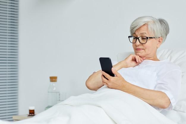 Bella donna senior rilassante sul letto in reparto ospedaliero, navigare in internet su smartphone Foto Premium