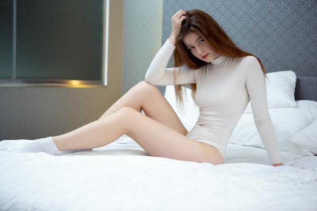 Una bella donna sexy in un body bianco si siede su un letto raddrizzato Foto Premium