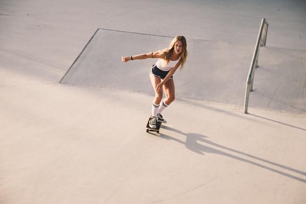 Momenti di lifestyle di bella ragazza skater in uno skatepark Foto Premium