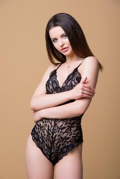 Bella ragazza bruna sexy esile in tuta di pizzo nero isolato su sfondo beige. Foto Premium