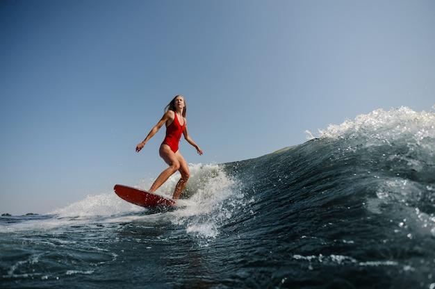 Bella donna esile che pratica il surfing su un'onda blu alta Foto Premium