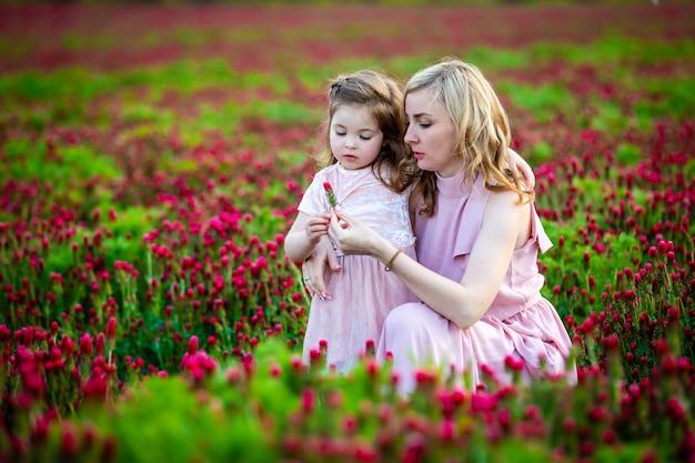 La bella ragazza sorridente del bambino con la giovane madre in famiglia guarda nel campo dei fiori del trifoglio nel tempo del tramonto Foto Premium