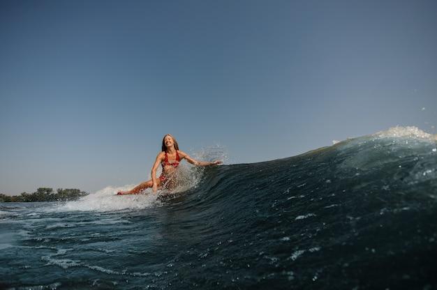 Bella donna sorridente che pratica il surfing su un'onda blu alta Foto Premium