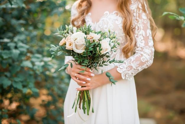 Bellissimo bouquet da sposa nelle mani della sposa. rosa, rosa e pesca. fiori matrimonio alla moda e moderni. donna in abito da sposa all'aperto Foto Premium