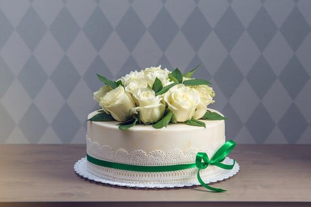 Bella torta nuziale bianca decorata con bouquet di fiori rose bianche Foto Premium