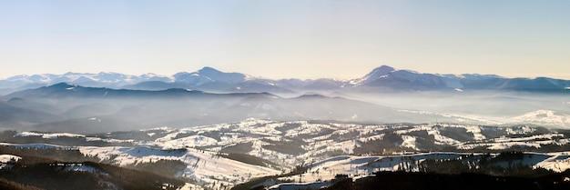 Bellissimo panorama invernale con neve fresca. paesaggio con abeti rossi, cielo blu con luce solare e alte montagne dei carpazi sullo sfondo. Foto Premium