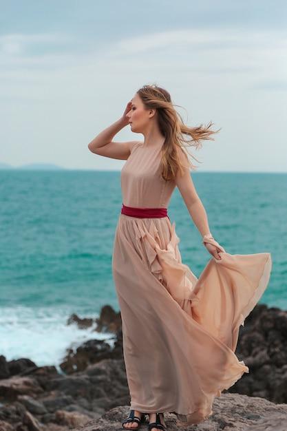 La bella donna in un vestito beige sta su una spiaggia rocciosa Foto Premium