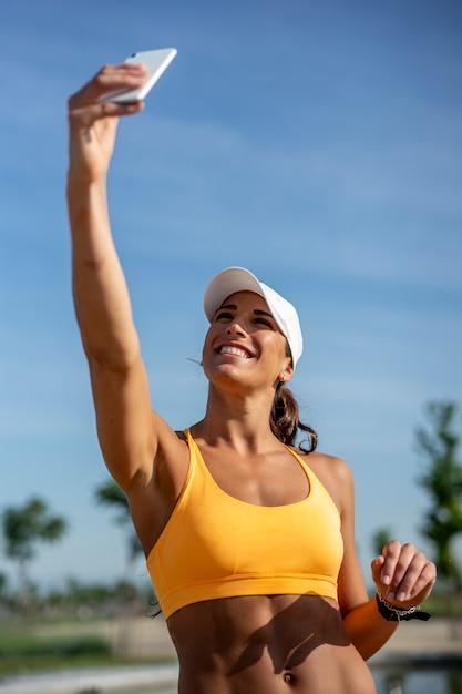 La bella donna si è vestita negli sport facendo uso del telefono cellulare mobile. Foto Premium
