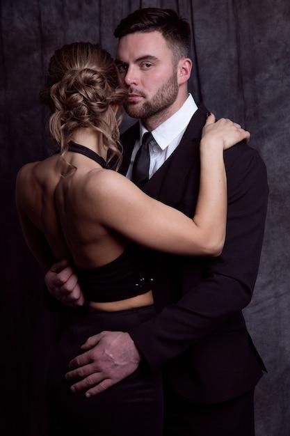 Una bella donna in abito da sera abbraccia un uomo elegante che cerca di baciarla Foto Premium