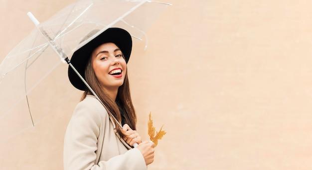 Bella donna che tiene un ombrello con lo spazio della copia Foto Premium