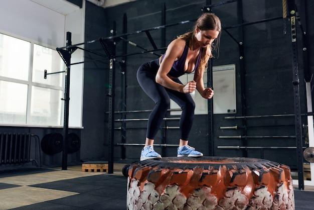 Bella donna che salta su una gomma enorme nella palestra di crossfit Foto Premium