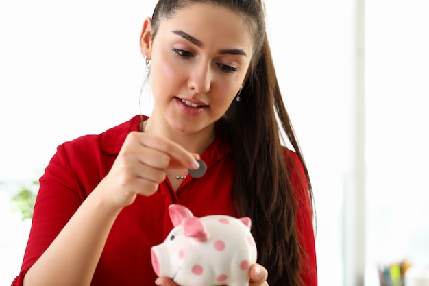La bella donna mette la moneta nel salvadanaio in ceramica Foto Premium