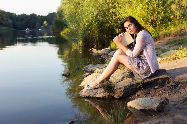 Bella donna che legge un libro nel parco Foto Premium