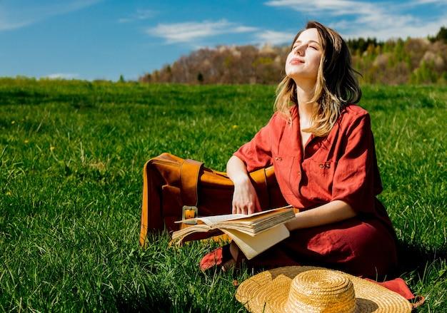 Bella donna in vestito rosso con la valigia e il libro che si siede sul prato Foto Premium