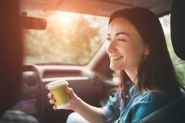 Bella donna che sorride mentre sedendosi sui sedili del passeggero anteriore in macchina e lei sta bevendo il caffè da una tazza usa e getta Foto Premium