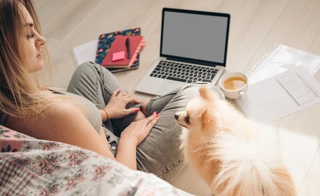 La bella donna lavora da casa. il cane la aiuta. lo spitz di pomerania si trova nelle vicinanze. Foto Premium