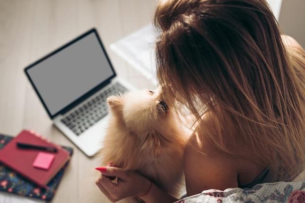 La bella donna lavora da casa con documenti e laptop. il cane la aiuta. la ragazza bacia il suo spitz pomeranian. Foto Premium