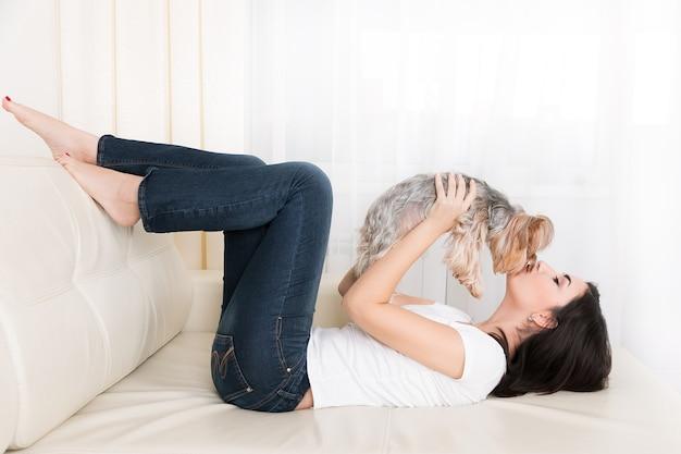 Bella giovane ragazza castana che gioca con il suo yorkshire terrier a casa che stabilisce al divano e bacia il suo animale domestico Foto Premium