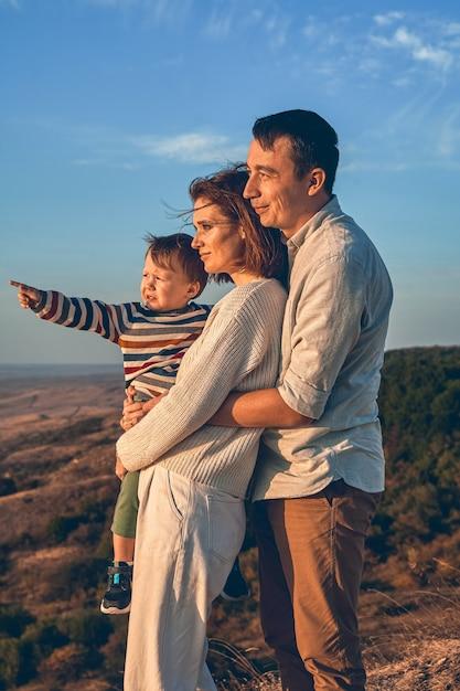 Bella giovane famiglia con un bambino piccolo in una passeggiata autunnale Foto Premium