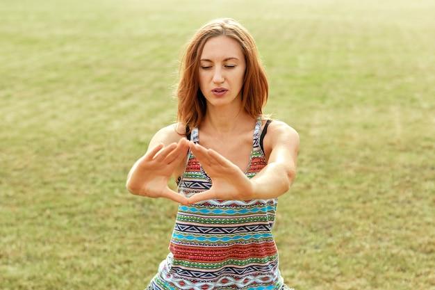 La bella giovane femmina si rilassa nella posa di yoga nella natura verde. donna di bellezza che fa yoga. concetto sano e yoga. fitness e sport Foto Premium