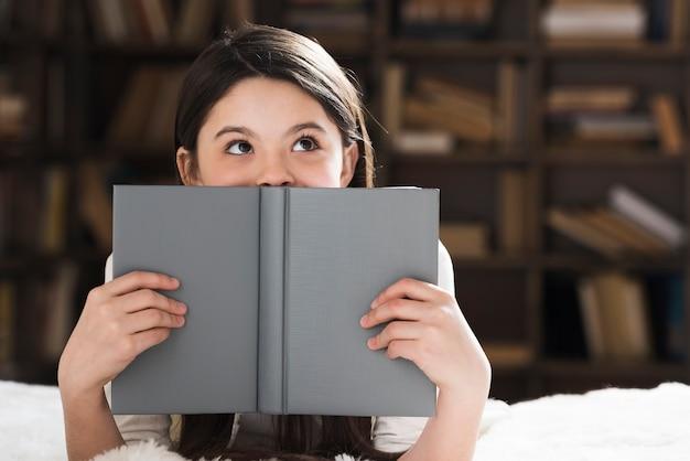 Bella ragazza che tiene un libro Foto Premium