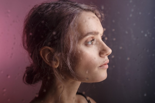 Bella ragazza guarda lontano su sfondo viola. gocce d'acqua sfocate corrono giù per il vetro davanti al suo viso Foto Premium