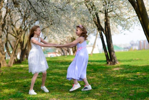 Belle ragazze con gli occhi azzurri in vestiti bianchi nel giardino con gli alberi di mele che sbocciano divertendosi e godendo dell'odore del giardino di fioritura della molla. Foto Premium