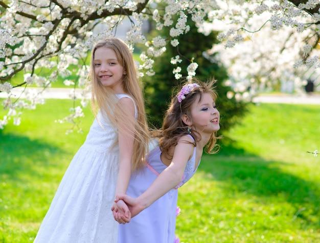 Belle ragazze con gli occhi azzurri in abiti bianchi in giardino con alberi di mele in fiore divertendosi Foto Premium