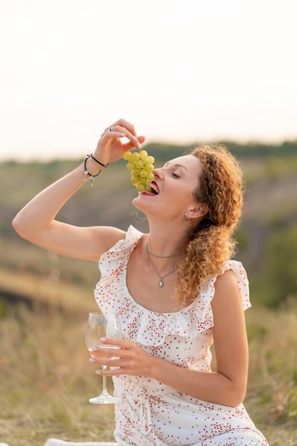 Bella giovane ragazza tenera dai capelli rossi in un prendisole bianco, mangia uva e beve vino sulla natura. Foto Premium