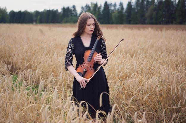 Bella giovane donna triste in piedi su un campo di grano preme un violino Foto Premium