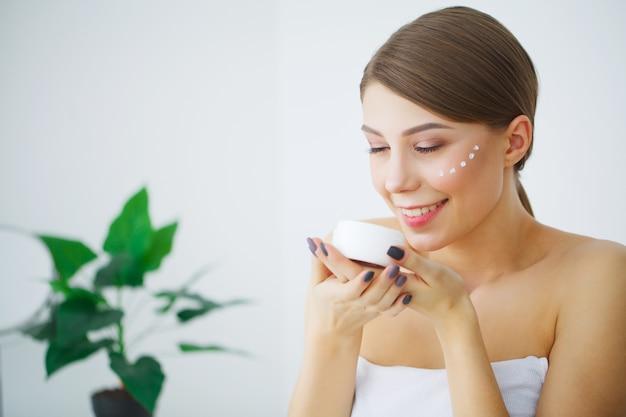 La bella giovane donna sorridente con pelle fresca pulita distoglie lo sguardo, cura del viso di bellezza della ragazza Foto Premium
