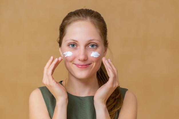 Bella giovane donna che applica cosmetici per il viso con le sue mani Foto Premium