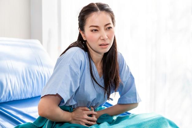 Paziente asiatico della bella giovane donna con dolore mestruale sulla stanza del letto di ospedale. Foto Premium