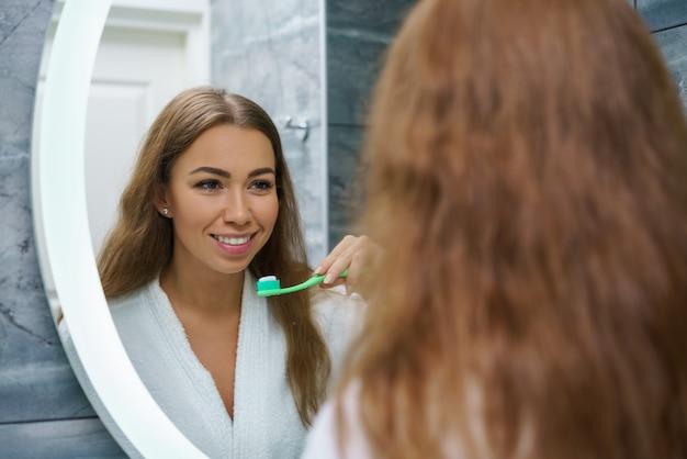 Una bellissima giovane donna si lava i denti e si guarda allo specchio Foto Premium