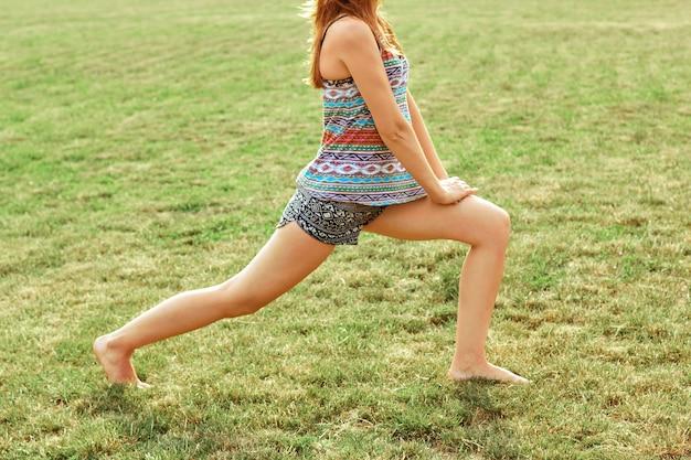 Bella giovane donna che fa gli esercizi nel parco. concetto sano e yoga. fitness e sport Foto Premium