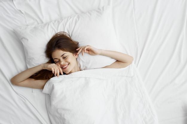 La bella giovane donna nel suo bellissimo letto bianco come la neve rilassa e rilassa, Foto Premium