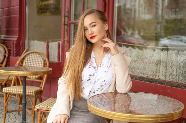 Bella giovane donna in un caffè parigino di strada Foto Premium