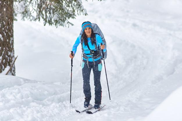 Una bella giovane donna che pratica da sola lo sci escursionistico Foto Premium