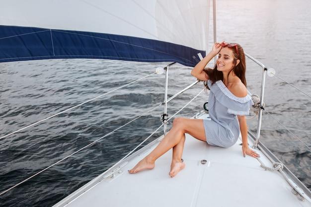 La bella giovane donna si siede sulla ciotola e sulle pose dell'yacht. tiene gli occhiali rossi sulla testa con la mano e il sorriso. il modello sta navigando a bordo dello yacht. Foto Premium