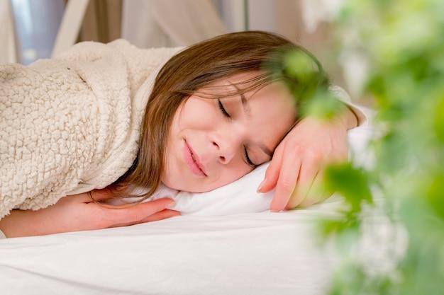 Bella giovane donna che dorme con il cuscino comodo. Foto Premium